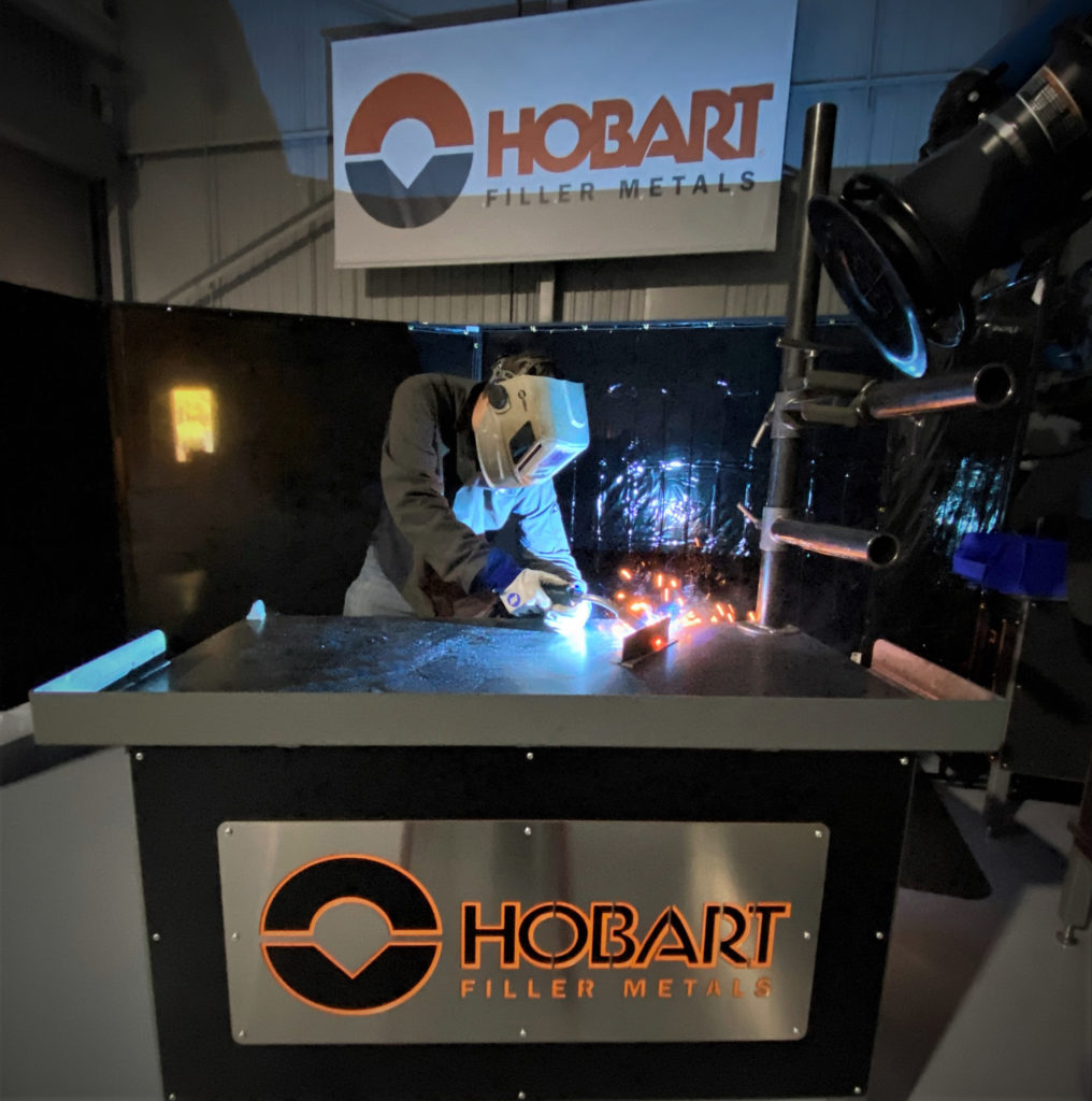 Welder MIG welding a thin weld coupon on a table with Hobart banner behind him